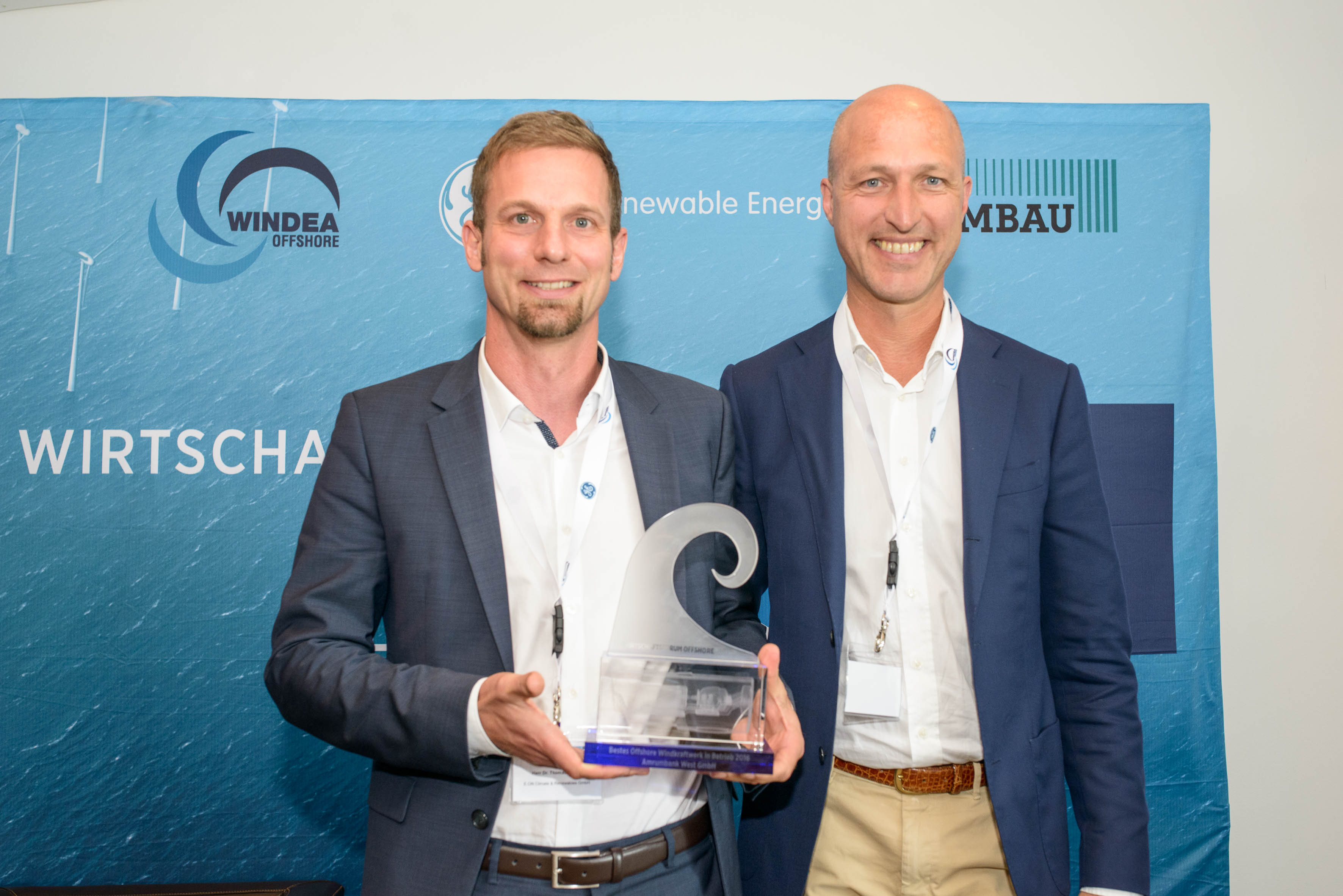 "Dr. Thomas Michel, Head of Operations Offshore Wind Nordic & Germany E.ON und Sven Utermöhlen, COO der E.ON Climate & Renewables GmbH mit der Auszeichnung ""Bestes Offshore Windkraftwerk in Betrieb 2016"""